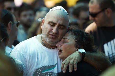 The mother of Israeli soldier Tal Yifrah mourns during her son's funeral near Tel Aviv