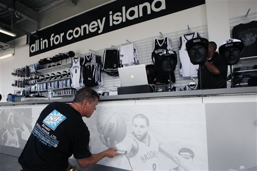 Barry Schmid applies a photo display to the sales counter inside the new Nets Shop by Adidas in the Coney Island neighborhood of Brooklyn in New York, Thursday, May 23, 2013. The shop, which carries a
