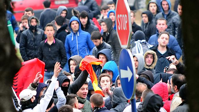 A group of ethnic Albanians tear apart Macedonian flag during a violent protest in Skopje, Macedonia, Saturday, March 2, 2013. Hundreds ethnic Albanians staged on Saturday a contra-protest to express support for the designation of the new defense minister. Police said Saturday at least 20 people, from whom 13 police officers and other mainly youngsters were injured in a series of scuffles that erupted late on Friday and continued over night when group of few hundred Macedonians started a protest against the designation of a new defense minister Talat Xhaferi, an ethnic Albanian and former rebel commander. (AP Photo/Vangel Tanurovski)