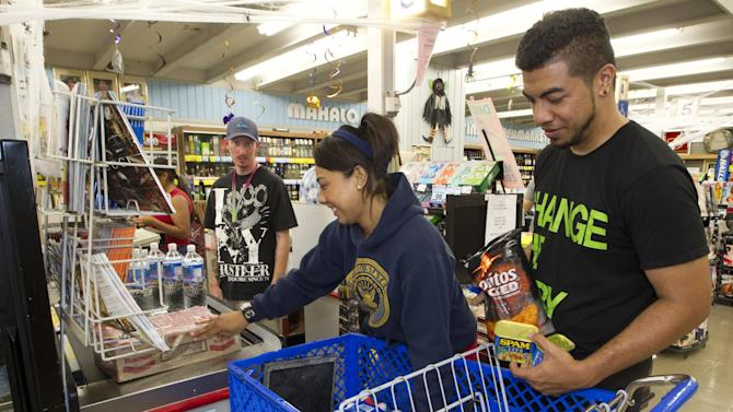 Erica Avegalio, center, and her brother Albert Avegalio, right, load up on water and food at the Times Supermarket after learning of a tsunami warning Saturday, Oct. 27, 2012, in Honolulu.  A tsunami warning has been issued for Hawaii after a 7.7-magnitude earthquake rocked an island off the west coast of Canada. The Pacific Tsunami Warning Center originally said there was no threat to the islands, but a warning was issued later Saturday and remains in effect until 7 p.m. Sunday. A small craft advisory is in effect until Sunday morning. (AP Photo/Eugene Tanner)
