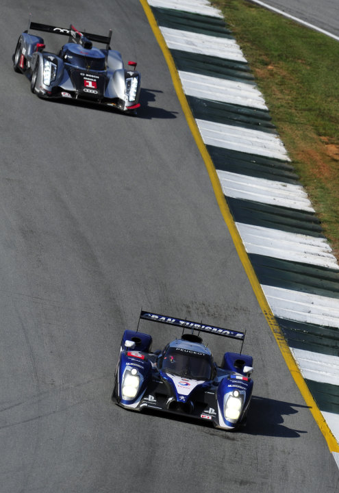Peugeot driver Franck Montagny, of France, leads the Audi of Romain Dumas, also of France, as they go through a corner during practice for the American Le Mans Series' Petit Le Mans auto race at Road