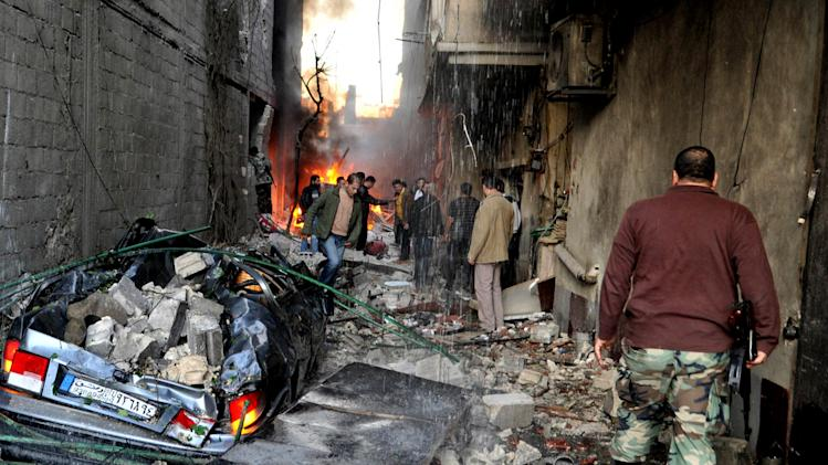 In this photo released by the Syrian official news agency SANA, a Syrian soldier, right, and citizens gather at an alley that was destroyed by two cars bombs, at Jaramana neighborhood, in the suburb of Damascus, Syria, Wednesday, Nov. 28, 2012. (AP Photo/SANA)