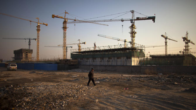 In this Jan. 17, 2013 photo, a man walks outside a construction site of a residential real estate project in Beijing, China. China's economy rebounded in the final quarter of 2012 but optimism was tempered by warnings the shaky recovery could be vulnerable to a possible downturn in global trade. (AP Photo/Alexander F. Yuan)