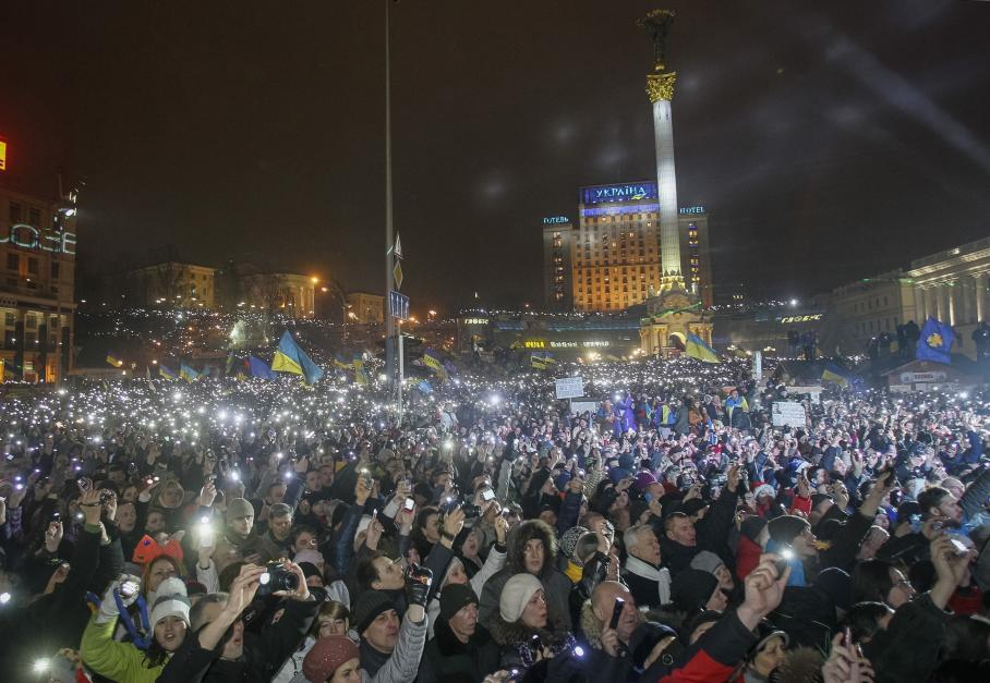Pro-European integration supporters hold up their mobile phones and flashlights as they sing the Ukrainian national anthem during New Year celebrations in Independence Square in central Kiev
