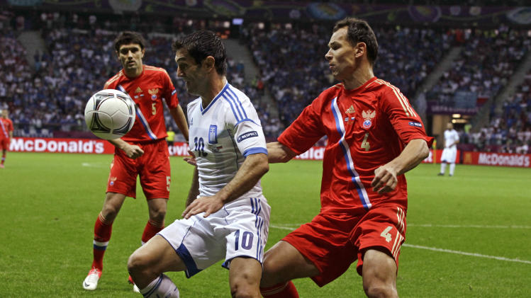 Greece's Giorgos Karagounis, left, and Russia's Sergei Ignashevich challenge for the ball during the Euro 2012 soccer championship Group A  match between Greece and Russia in Warsaw, Poland, Saturday, June 16, 2012. (AP Photo/Sergey Ponomarev)