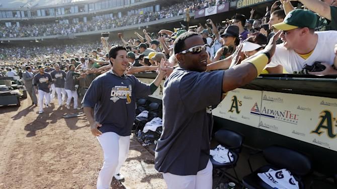 Oakland Athletics' Yoenis Cespedes, right, and Tommy Milone celebrate with fans after their 12-5 win over the Texas Rangers in a baseball game, Wednesday, Oct. 3, 2012 in Oakland, Calif. The A's clinched the AL West title with the win. (AP Photo/Marcio Jose Sanchez)