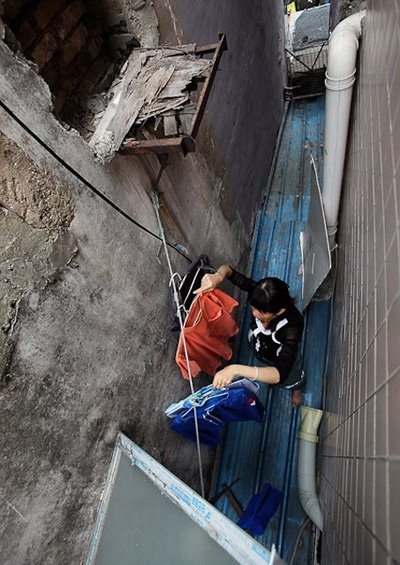 Wang Xuanna has to climb out of the loft to dry their clothes in the gap between two buildings.