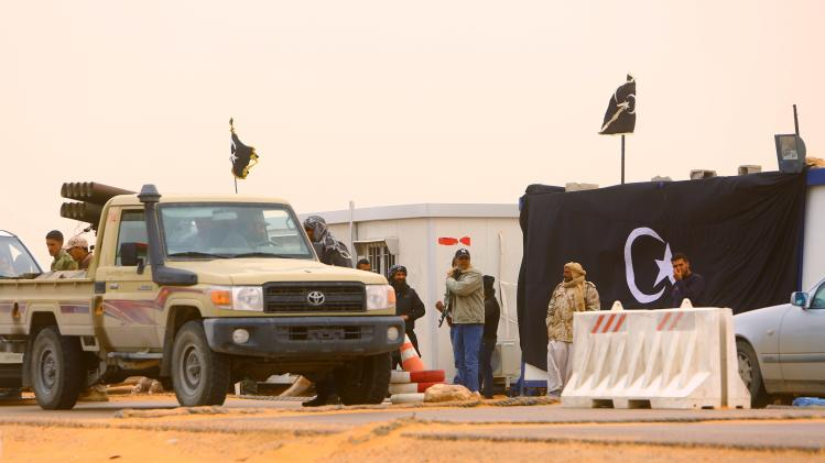 Heavily armed vehicles belonging to the military council of the self-declared autonomous region of Cyrenaica, drive past a flag of the region at a checkpoint, near Sirte
