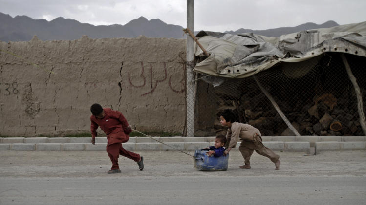 Afghan boys play on a road on the outskirts of Kabul, Afghanistan, Monday, April 29, 2013. (AP Photo/Rahmat Gul)