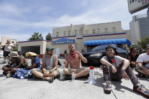 A few demonstrators sit on a Domino's Pizza parking lot in protest, Thursday, Aug. 30, 2012, in Tampa, Fla. The three dozen chanting anti-GOP protesters hit a lull of silence as they marched through a