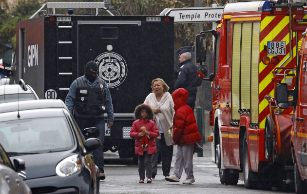 A woman and children are escorted by a police officer near a building where the chief suspect in an al-Qaida-linked killing spree is holed up in an apartment in Toulouse, France Thursday March 22, 201