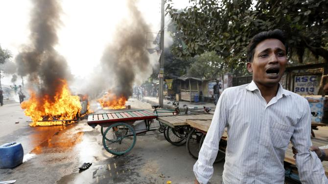 A man cries after Jamaat-e-Islami party activists torched his vehicle during a clash with police in Dhaka