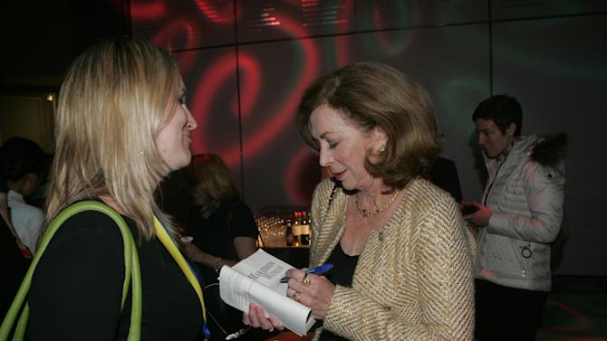 Kathrine Switzer, the first woman to register for and run the Boston Marathon signs a copy of her book for fan Jessica Donovan at a special cocktail party as AOL, PBS and Simple Celebrate MAKERS, on Tuesday, Nov. 20, 2012 in Brighton, Mass. (Photo by Aynsley Floyd/Invision for AOL and PBS/AP Images)