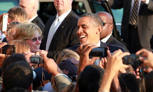 President Barack Obama greets well-wishers as he arrives at JFK International Airport in New York, Wednesday, Aug. 22, 2012, on his way to a visit in New York City where he attends several fundraiser events. (AP Photo/David Karp)