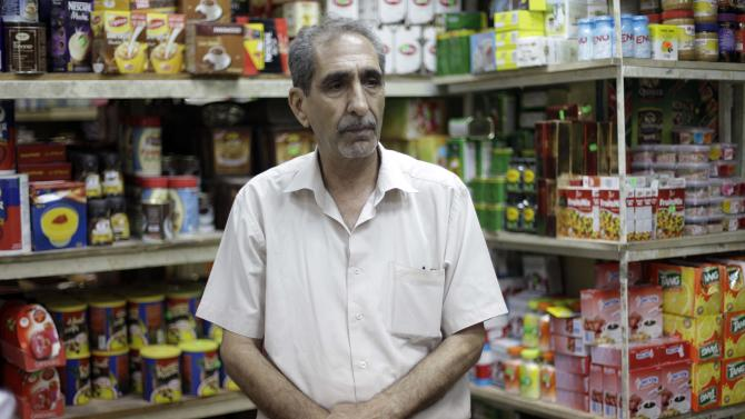 "Abdul Hadi al-Obeidi, 65, a Sunni Muslim and is married to a Shiite woman who manages a grocery store in the Karrada Neighborhood of Baghdad, Iraq, poses for a portrait  Wednesday, July 4, 2012. ""Every time I leave my house, I don't know what will happen to me. I can only leave it in God's hands,"" he said. (AP Photo/Khalid Mohammed)"
