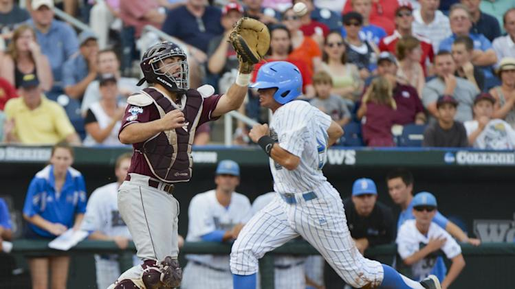 UCLA's Brian Carroll, right, scores at home plate ahead of the throw to Mississippi State catcher Nick Ammirati on a single by Eric Filia in the first inning of Game 2 in their NCAA College World Series baseball finals, Tuesday, June 25, 2013, in Omaha, Neb. (AP Photo/Ted Kirk)