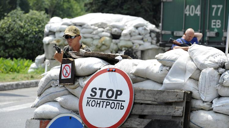 Pro-Russian separatists stand guard at a check-point near the eastern Ukrainian city of rebel stronghold Donetsk on July 23, 2014