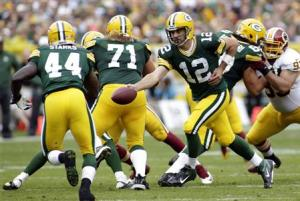 Green Bay Packers quarterback Rodgers hands off the ball to running back Starks during the first half of their NFL football game against the Washington Redskins in Green Bay