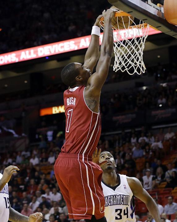 Miami Heat's Chris Bosh (1) dunks over Sacramento Kings' Jason Thompson (34) in the first half of an NBA basketball game, Friday, Dec. 20, 2013, in Miami
