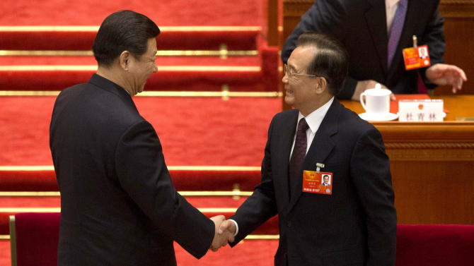 Newly-named Chinese President Xi Jinping, left, shakes hands with former Premier Wen Jiabao after a plenary session of the National People's Congress during which Li Keqiang was announced to be the nation's new premier at Beijing's Great Hall of the People Friday, March 15, 2013. (AP Photo/Alexander F. Yuan)