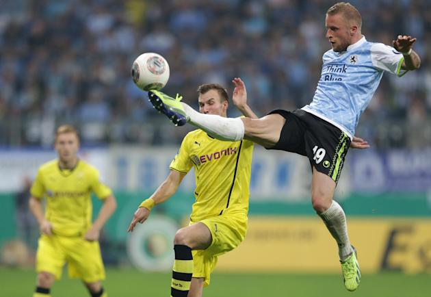 Munich's Daniel Adlung, right, and Dortmund's Kevin Grosskreutz challenge for the ball during the German soccer cup second round match between TSV 1860 Munich and Borussia Dortmund, in Munich, souther