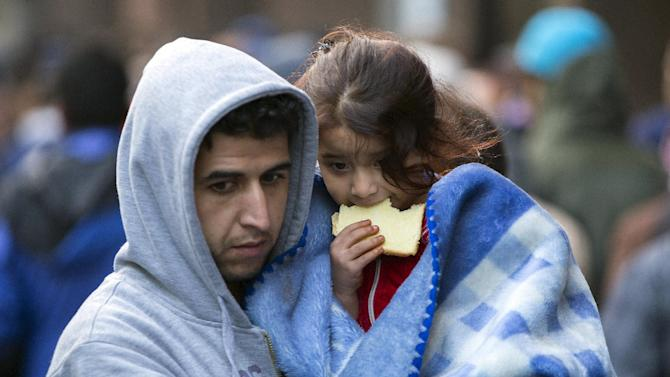 A young asylum seeker eats bread in the arms of her father outside the foreign office in Brussels