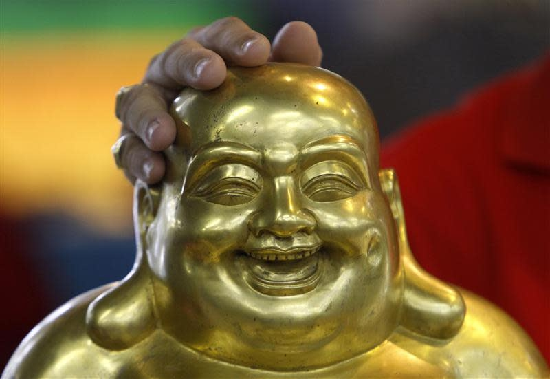 Store employee Jeffrey puts his hand on a gold and porcelain Buddha statue that the store had valued at S$38,888 ($34083) at a Cash Converters used goods store in Singapore