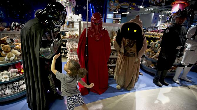 """A man dressed as Darth Vader from """"Star Wars"""" high fives a child as people arrive to purchase toys that went on sale at midnight in advance of the film """"Star Wars: The Force Awakens"""" in Times Square in New York"""