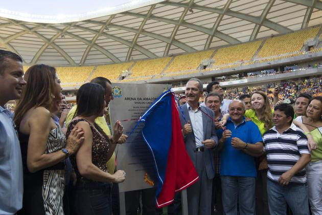 Brazil's Sports Minister Aldo Rebelo uncovers the plaque commemorating the inauguration of the Arena Amazonia Vivaldo Lima soccer stadium in Manaus