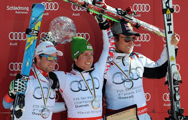 Overall World Cup winner Austria's Marcel Hirscher (C) holds his crystal globe as he poses with second-placed Switzerland's Beat Feuz (L) and third-placed Norway's Aksel Lund Svindal on the podium of