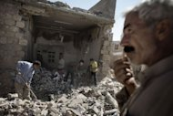 Syrians sift through the rubble of houses following an air raid by regime forces in Al-Bab. Fighting raged in Syria's two biggest cities on Sunday as UN-Arab League envoy Lakhdar Brahimi ended his first visit to the country on a peace mission a rebel commander said was doomed to fail