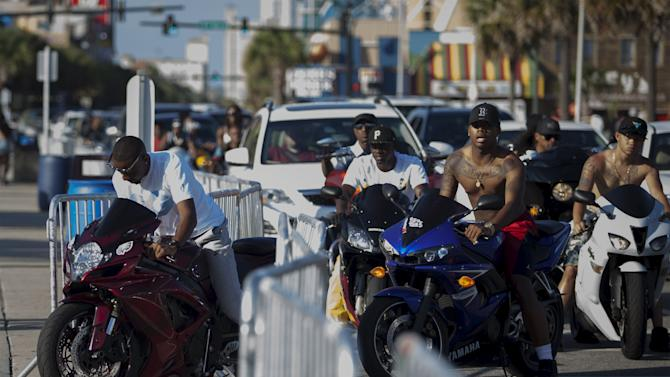 Bikers ignore a fenced boundary after having engine problems from a overheated motorcycle on Ocean Boulevard during the 2015 Atlantic Beach Memorial Day BikeFest in Myrtle Beach