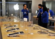 <p>File photo of employees at an Apple store in Tokyo. Apple was seeking 100 million yen ($1.27 million) in compensation from Samsung's Japanese units, and had accused it of stealing technology used to transfer music and video files.</p>