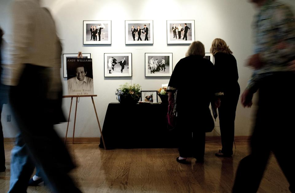 "Patrons of Andy Williams' memorial service look at pictures of Williams at the Moon River Theater, in Branson, Mo., Sunday, Oct. 21, 2012. Williams, known for singing ""Moon River"" and his Christmas television specials, passed away Sept. 25. (AP Photo/Grant Hindsley)"