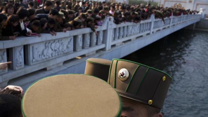 North Korean soldiers and civilians stand on a foot bridge to look at goldfish in a moat as they tour the grounds of Kumsusan Palace of the Sun, the mausoleum where the bodies of the late leaders Kim Il Sung and Kim Jong Il lie embalmed, in Pyongyang on Thursday, April 25, 2013. North Korea on Thursday marked the 81st anniversary of the founding of its military, which began as an anti-Japanese militia and now has an estimated 1.2-million troops. (AP Photo/David Guttenfelder)