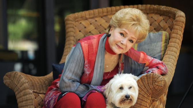 """In this Tuesday, May 21, 2013 photo, Debbie Reynolds, a cast member in the film """"Behind the Candelabra,"""" poses for a portrait with her dog, Dwight, in Beverly Hills, Calif. Reynolds plays Frances, the mother of the pianist and vocalist, Liberace. HBO debuts """"Behind the Candelabra"""" in the US, Sunday, May 26, 2013. (Photo by Chris Pizzello/Invision/AP)"""