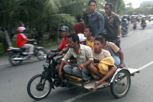 Acehnese men ride on a motorized pedicab as they evacuate to higher ground after a strong earthquake was felt in Banda Aceh, Aceh province, Sumatra island, Indonesia, Wednesday, April 11, 2012. Two ma