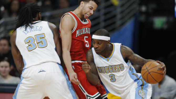 Milwaukee Bucks guard Michael Carter-Williams, center, reacts as he gets squeezed between a pick set by Denver Nuggets forward Kenneth Faried, left, and a drive to the basket by guard Ty Lawson during the first quarter of an NBA basketball game Tuesday, March 3, 2015, in Denver. (AP Photo/David Zalubowski)