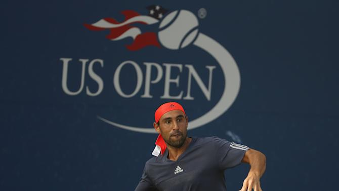 Baghdatis returns to Darcis in their first round match at the U.S. Open Championships tennis tournament in New York