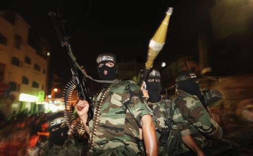 Palestinian Hamas militants celebrate news of a prisoner swap between Hamas and Israel, at Jabalya, in the northern Gaza Strip
