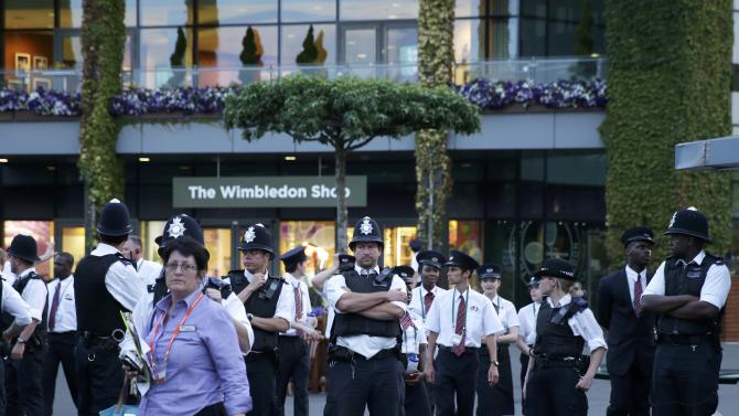 Police evacuate the area after a fire broke out inside Centre Court in Wimbledon at the end of play during the Tennis Championship, in London