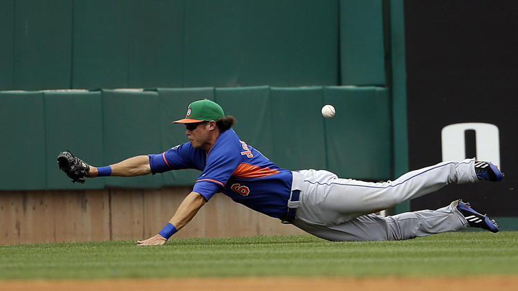 New York Mets' Matt den Dekker misses a fly ball hit by Miami Marlins' Garrett Jones for a double in the third inning of an exhibition spring training baseball game, Monday, March 17, 2014, in Jupiter, Fla. (AP Photo/David Goldman)