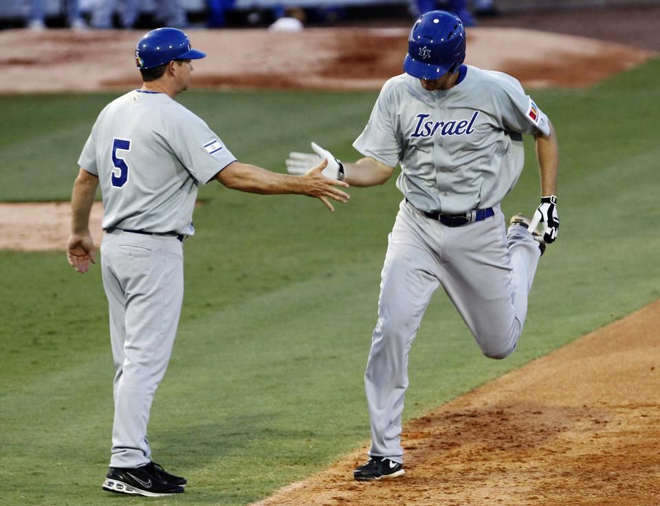 Israel's Nate Freiman, right, is congratulated by third base coach Mark Loretta (5) after hitting a home run against South Africa in the first inning of a World Baseball Classic qualifier baseball game in Jupiter, Fla., Wednesday, Sept. 19, 2012. (AP Photo/Alan Diaz)