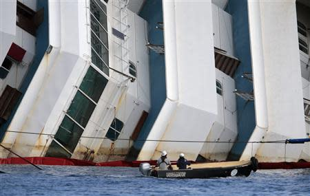 Salvage crew workers follow an operation to raise the capsized cruise liner Costa Concordia from a boat next to it, outside Giglio harbour