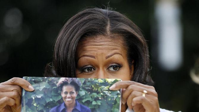 First lady Michelle Obama holds up a copy of her book as she talks about the White House Kitchen Garden, Tuesday, June 5,2012, on the South Lawn of the White House in Washington. (AP Photo/Charles Dharapak)