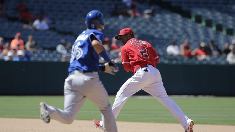 Los Angeles Angels' Erick Aybar, right, looks to throw to first base as Toronto Blue Jays' Munenori Kawasaki, of Japan, runs toward second base during the seventh inning of a baseball game on Wednesday, July 9, 2014, in Anaheim, Calif. (AP Photo/Jae C. Hong)