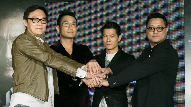 """In this photo taken on Monday, Nov. 12, 2012, Hong Kong director Sunny Luk,  left, actors Tony Leung Ka Fai, second from left, Aaron Kwok, center, and director Lok Man Leung pose for media during a promotional event for their new film """"Cold War"""" in Taipei, Taiwan. (AP Photo/Chiang Ying-ying)"""
