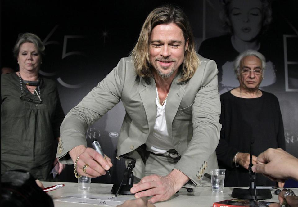 Actor Brad Pitt, centre signs an autograph during a press conference for Killing Them Softly at the 65th international film festival, in Cannes, southern France, Tuesday, May 22, 2012. (AP Photo/Francois Mori)