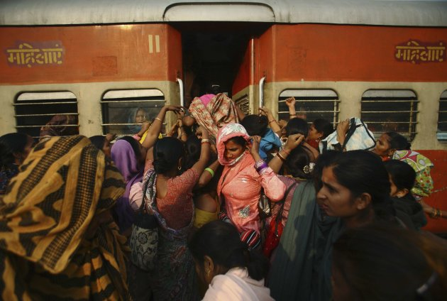 Women try to enter the ladies' compartment of a crowded train heading towards Delhi at Noli Railway Station in Utter Pradesh