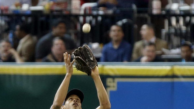Houston Astros center fielder Justin Maxwell makes the catch and the out on Texas Rangers' Mitch Moreland in the fourth inning of a baseball game, Wednesday, April 3, 2013, in Houston. (AP Photo/Pat Sullivan)